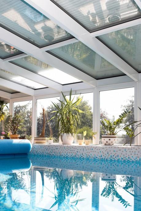 Předokenní rolety střešního typu: Předokenní rolety na střešním skle chránící bazén před sluncem