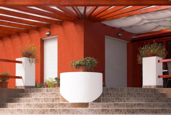 Předokenní rolety v kombinaci s oranžovou fasádou: Předokenní rolety jsou dekoračním doplňkem jakéhokoliv exteriéru