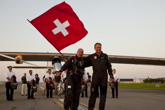 Bertrand Piccard a Andre Borschberg po přistání ve Švýcarsku, v pozadí solární letadlo Solar Impulse; foto: © Solar Impulse | Laurent Kaeser