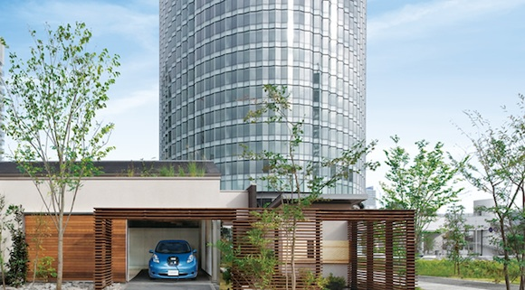 elektromobil Nissan Leaf nabíjí rodinný dům, v pozadí mrakodrap